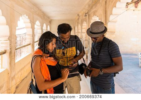JODHPUR RAJASTHAN INDIA - MARCH 05 2016: Horizontal picture of two indians men with a western tourist at Mehrangarh Fort in Jodhpur the blue city of Rajasthan in India.