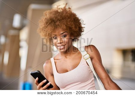 happy african american woman with smartphone at airport smiling at camera