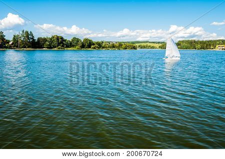 Small yacht sailing on lake with people. Beatiful summer landscape view from sailing boat. Sunny summer day with nice blue sky waves on water surface forest and meadow on the other side.