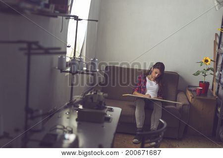 Young fashion designer making sketches of new clothing designs in her atelier