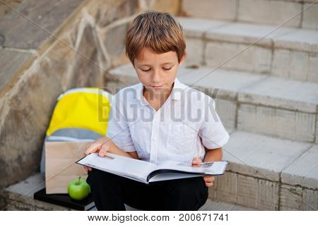 A small schoolboy reading a book with a homework on the stairs of the school. Next is a package and a package with breakfast