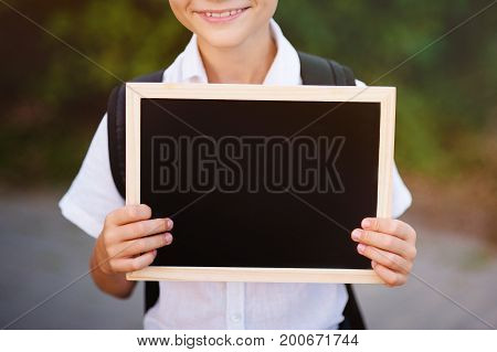 The schoolboy holds an empty chalkboard for writing.