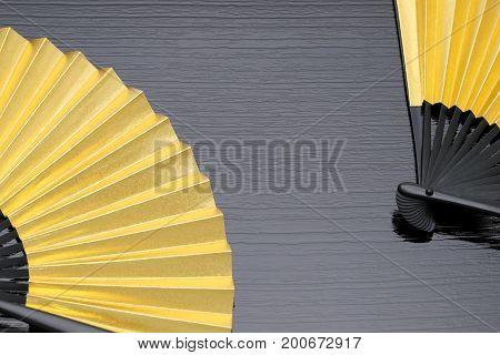 traditional golden folding fan on black background