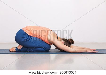 Woman relax in Hatha yoga asana Balasana - child's pose resting position or counter asana for many asanas on yoga mat on yoga mat in studio on grey bagckground