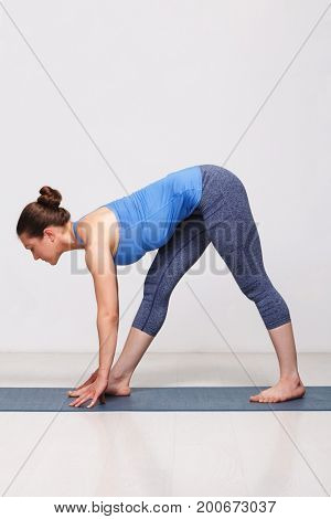Woman doing Ashtanga Vinyasa yoga asana Parsvottanasana - intense side stretch pose on yoga mat on yoga mat in studio on grey bagckground