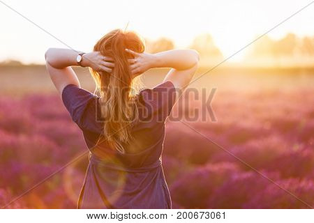 Young woman touching her long sombre hair looking at lavender field at sunset. Romantic warm sunshine