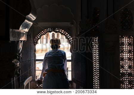 JODHPUR RAJASTHAN INDIA - MARCH 05 2016: Horizontal picture of indian man with turban looking at the window at Mehrangarh Fort in Jodhpur the blue city of Rajasthan in India.