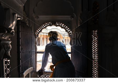 JODHPUR RAJASTHAN INDIA - MARCH 05 2016: Wide angle picture of indian man with turban looking at the window at Mehrangarh Fort in Jodhpur the blue city of Rajasthan in India.