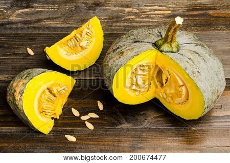 Slices of raw pumpkin on wooden background for cooking