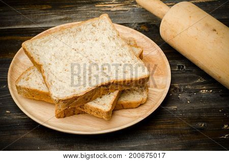 Slice whole wheat bread on wooden plate for eating,healthy food