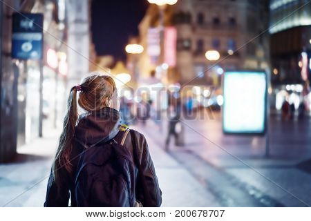 Back view of girl walking on city street at night, Prague
