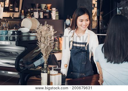 Asian woman barista wear jean apron holding coffee cup served to customer at bar counter with smile emotionCafe restaurant service conceptOwner small business concept.