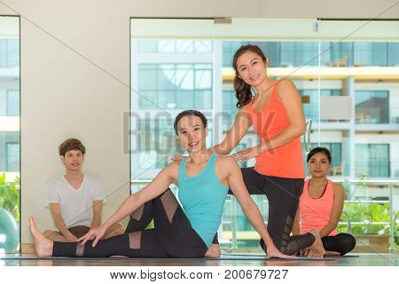 Asian woman yoga master teaching student in studio classroomWellness and Healthy Lifestyle