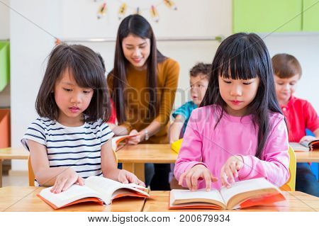 two Asian girl kid reading book in classroom and while teacher teach friends beside themkindergarten education.
