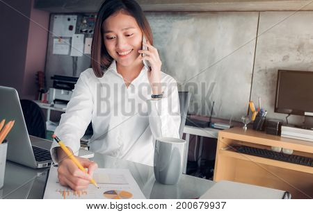 Asian businesswoman with smiling face talking on mobile and writing analyze business data on sheet on desk with colleague on phone Office life conceptworking woman at modern home office.