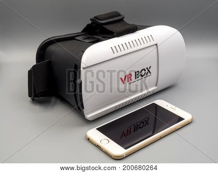 Chiang Rai Thailand: August 9 2017 - Packshot image of Apple iPhone and virtual reality headset (VR Box) on gray background
