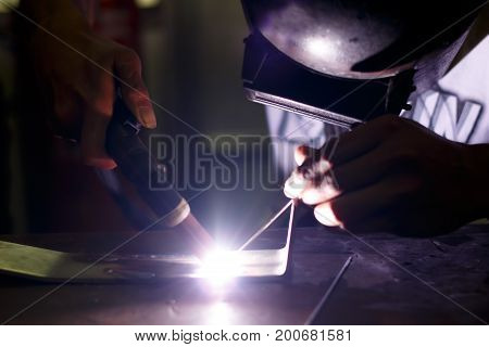 worker welding with groves and helmet protection