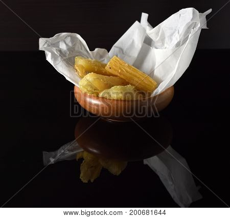 Close-up on several pieces of fried yucca in a wooden bowl on a reflective black surface