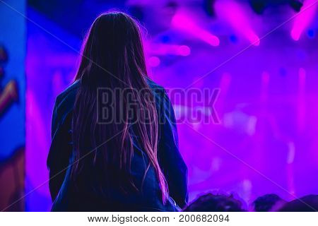 Silhouette Of A Big Crowd At Concert Against A Brightly Lit Stage. Night Time Rock Concert With Peop
