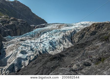 Exit Glacier In Seward Alaska, hikers off in a distance making their way toward the Glacier's edge.