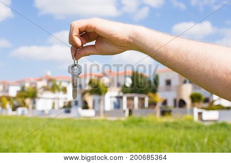 Holding house keys on house shaped keychain close up in front of a new home. Concept of real estate
