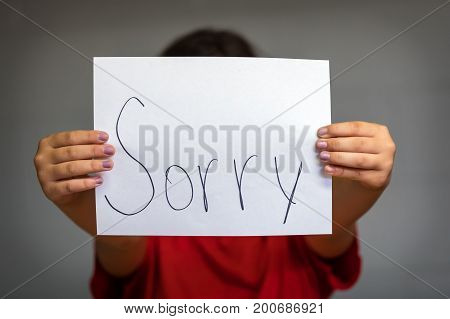 A girl holding up a paper saying sorry