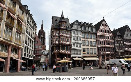 Frankfurt am Main Germany - Aug 2 2017. Traditional german decorated houses at the Frankfurt Old town square on cloudy summer day. The Imperial Cathedral of Saint Bartholomew in the background.