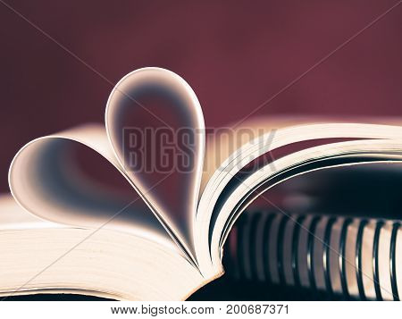 Closeup soft focus pages of a book curved into a heart shape. Love and Valentine's day concept.