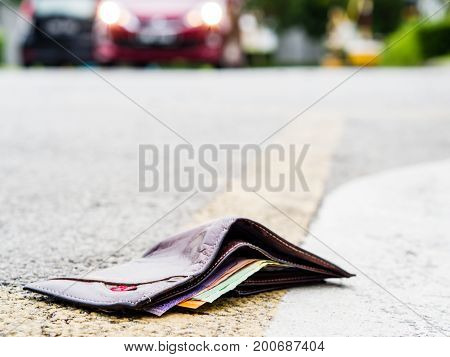 Lost leather wallet with money drop on the road lost money concept copy space on top.