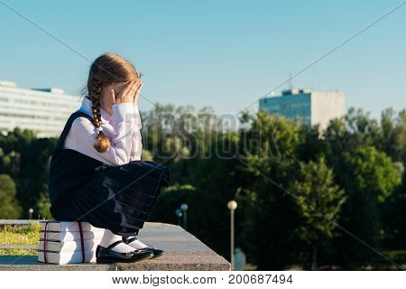 little schoolgirl sits on a textbook and cries does not want to study