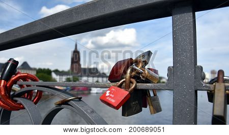 Frankfurt am Main Germany - Aug 2 2017. Colored padlocks on the iron bridge or Eiserner Steg as a token of love with the Imperial Cathedral of Saint Bartholomew in the background.