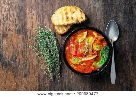 Minestrone with vegetables in bowl on a wooden table top view