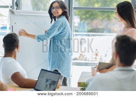 Training officer. Smart positive creative woman holding a highlighter and smiling while writing on the whiteboard
