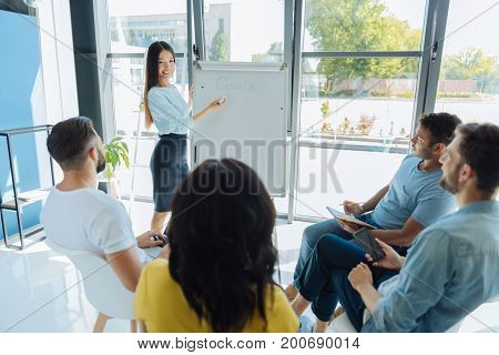 Professional development. Attractive positive young woman standing near the whiteboard and looking at her group while presenting information to them