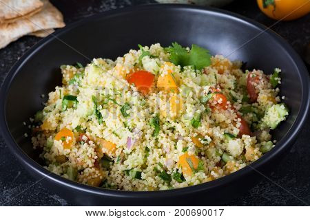 Lebanese arabic cuisine: healthy delicious salad with cous cous, fresh vegetables and greens called Tabbouleh in black bowl. Authentic food bowl