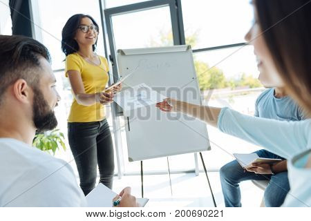 It is for you. Nice delighted intelligent woman standing near the flipchart and giving visual materials while conducting a business seminar