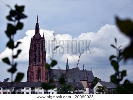 Frankfurt am Main Germany - Aug 2 2017. The view of the Imperial Cathedral of Saint Bartholomew over the grass. Gothic-style Catholic cathedral decorated with Renaissance frescoes.