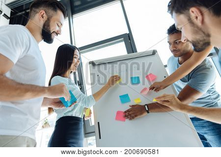 Being determined. Happy joyful young people holding sticky notes and putting them on the whiteboard while defining their notes
