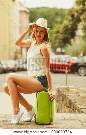 Hitch hiking and travelling. Lovely smiling cute girl sits on green suitcase luggage baggage waiting for car. Female hitch-hiker in hat travelling all around the world.
