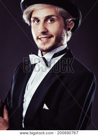 Tuxedo male fashion classical look concept. Elegantly dressed man wearing black fedora hat. Studio shot on dark background