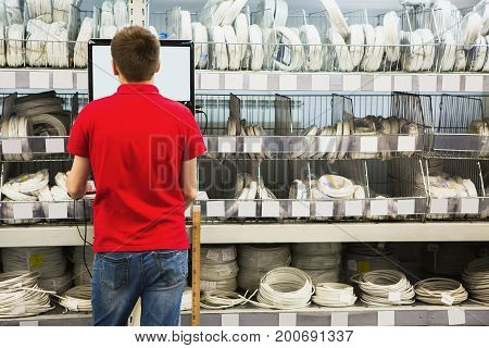Seller at the computer for inventory of products in hardware store.