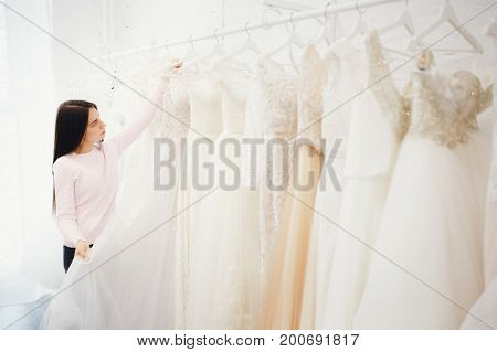 Woman choosing wedding dress in shop. Concept engagement, preparation for the main day of the girl.