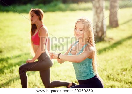 Girl is looking at a fitness bracelet, doing fitness in park with girlfriend. Concept team sports, sports and technology, application for the phone health.