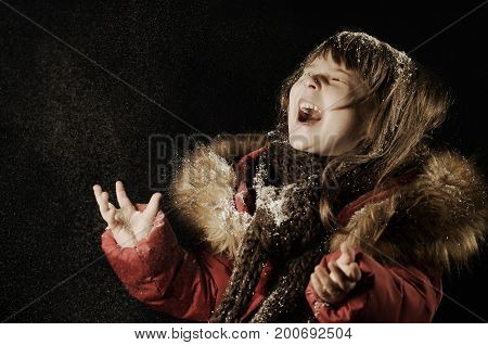 Little caucasian girl laughing happy for the falling snow. Snowfall