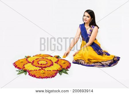 Indian woman or young girl making floral or flower rangoli for diwali or onam, isolated over white background