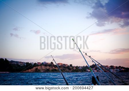 Few fishing rods on a sea settlement in background at sunset.