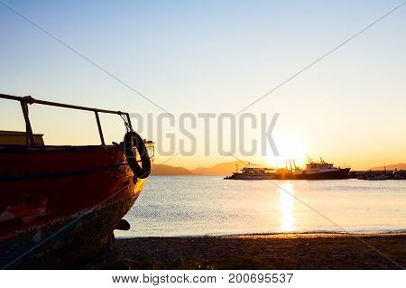 Silhouetted scenic view of old boat dry docked in a beautiful sunset at the beach coastline.
