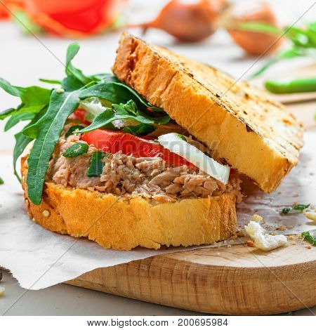 Delicious sandwich made of toasts tuna tomato onion and arugula with ingredients on a white table. Traditional healthy food.