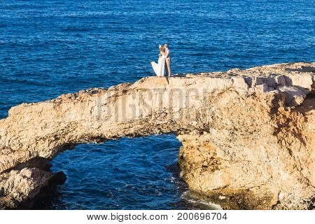 wedding in cyprus, bride and groom on a stone bridge in Agia Napa, cyprus.