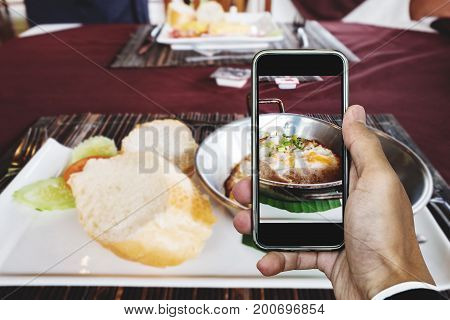 Taking food photography of homemade pan eggs fried and toasted bread, top view by smart phone